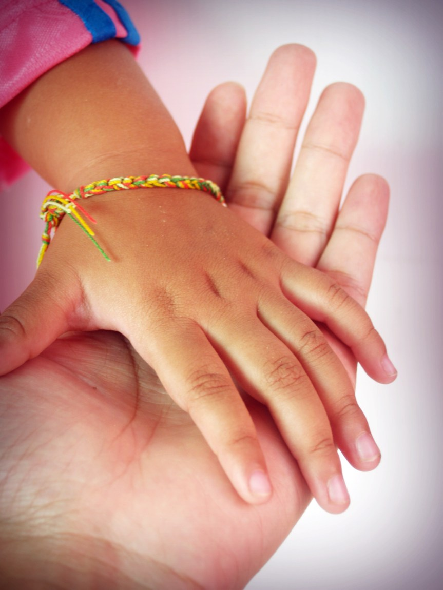 Hands holding the hand of a younger